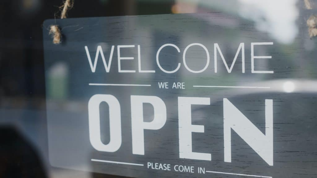 Welcome we're open vintage black and white retro sign on a coffee glass door cafe.
